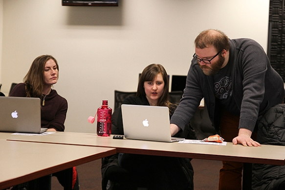 Andy Boyle helps Emily Brosious (left) and Melanie Stone with some code. (Photo/Brianna Kelly)